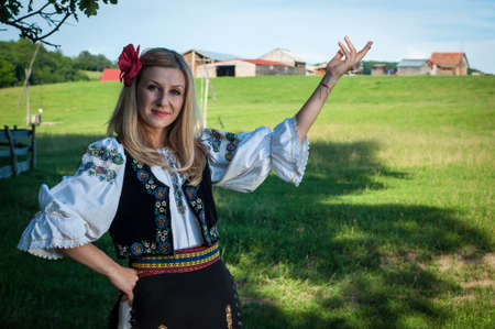 beautiful woman with red flower in her hair posing in Romanian traditional costume