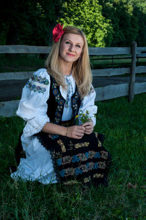 ethnology: beautiful singer with flowers posing in traditional costume, romanian folklore Stock Photo