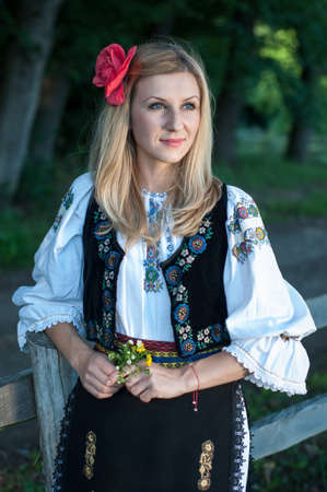 beautiful singer with flowers posing in traditional costume, romanian folklore Stockfoto
