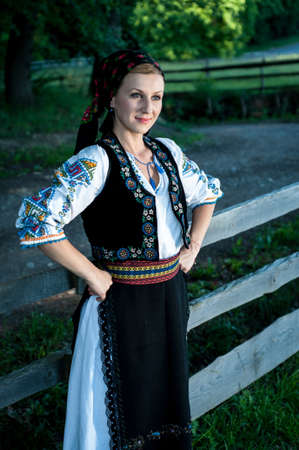 Portrait of young beautiful woman posing outside in Romanian traditional costume Stock Photo