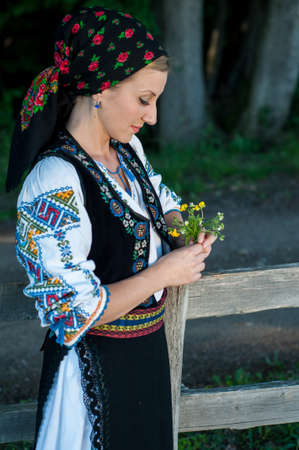beautiful singer with flowers in her hands posing at countryside, romanian folklore Stock Photo - 20896803