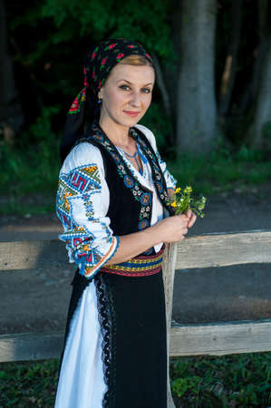 beautiful singer with flowers in her hands posing at countryside, romanian folklore Stock Photo - 20896808
