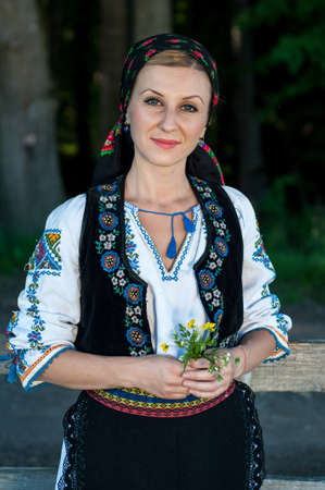 beautiful singer with flowers in her hands posing at countryside, romanian folklore photo