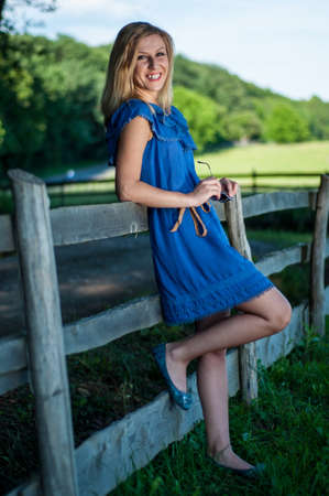 Young pretty blonde posing in summer field near a fence