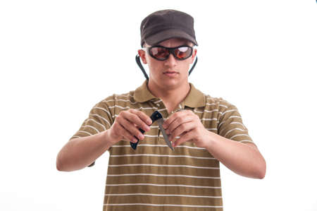 Burglar in with cap and sunglasses open a knife, focus on his hands