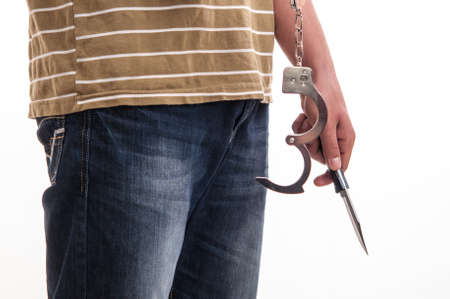 waiting convict: Close up of a man handcuffed with a knife in hand