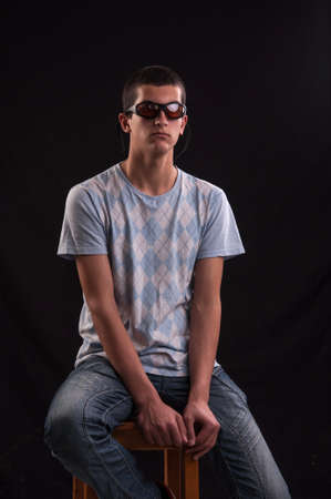 Serious young caucasian man with sunglasses sitting on chair