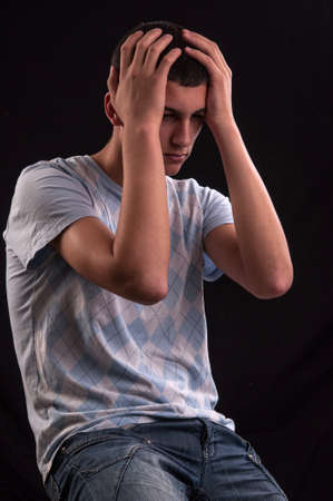 anguish: Upset teenager with head in hands wincing from stress, anguish or depression