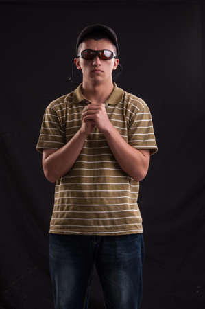 Serious and thoughtful teenage boy with sunglasses and baseball hat. Adolescent problems photo