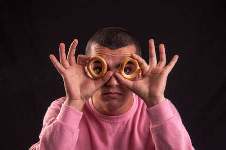 cheerful teenager look through a bagels hole photo