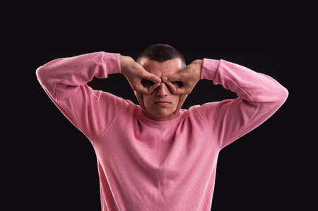 Young man searching something, making binoculars with his hands Stock Photo