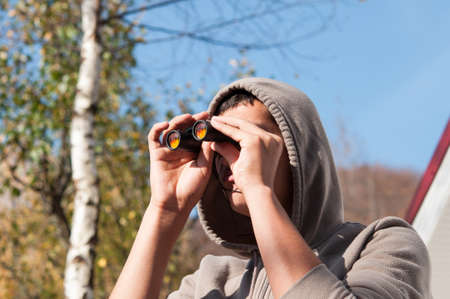 Young man with binoculars watching the nature, Man with binoculars photo