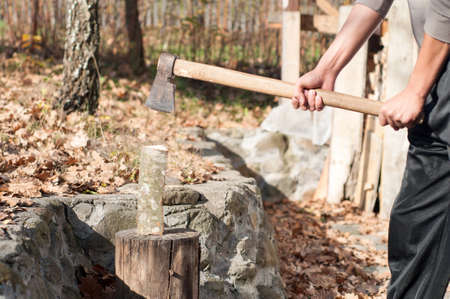 young man with an ax chops wood for heating Stock Photo