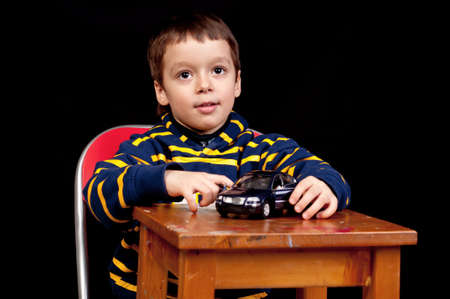 Smiling little boy plays indoor with toy car photo