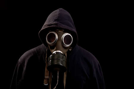 Man in black clothes wearing a classic gas mask over a dark