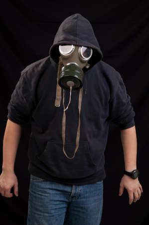 Man in black clothes wearing a classic gas mask over a dark background photo