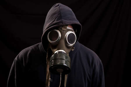 Man in black clothes wearing a classic gas mask over a dark background Stock Photo