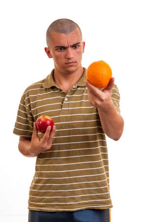 young man comparing orange to red apple photo