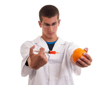 Toxin injection in orange with syringe. Genetically modified food (GMO) photo