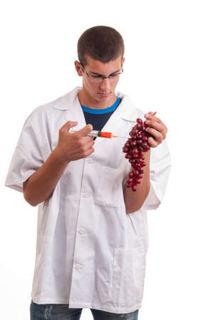 Injection into fruits. Genetically modified fruit with syringe by scientist. GMO food Stock Photo