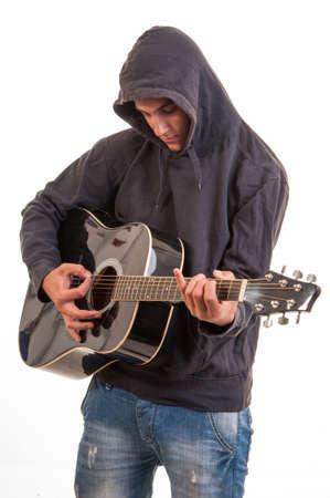 teenage problems: Adolescente triste en hoodie tocando la guitarra ac�stica. Tratar de escribir una canci�n sobre problemas de la adolescencia Foto de archivo