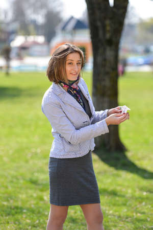 Excited cute woman counts money in the park, happy that she has just received salary