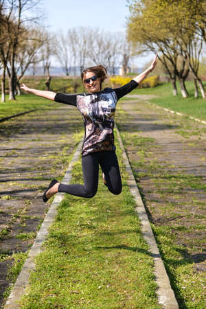 Pretty young woman jumping on green grass and smiling full of joy and vitality in summer or spring Stock Photo