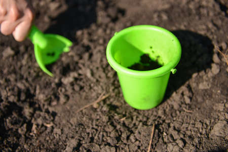 Girl playing in the mud with green toy bucket and spade photo