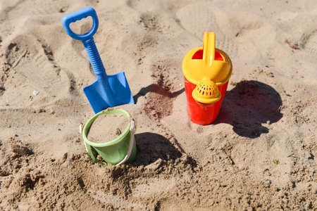 Colorful summer beach toys, bucket, sprinkler and shovel on sand on a sunny day photo