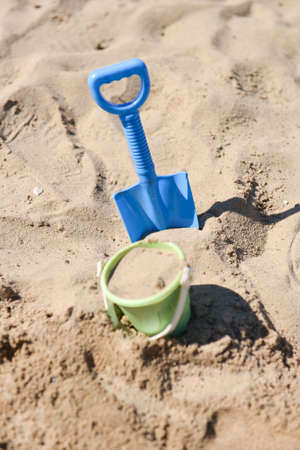 a beach bucket and a beach shovel stuck in the sand by a child photo
