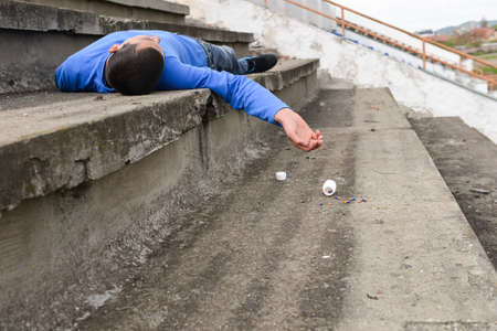 teenager committing suicide with pills. he is lying on the stairs of a stadium with a bottle and pills fallen down. Selective focus Stock Photo