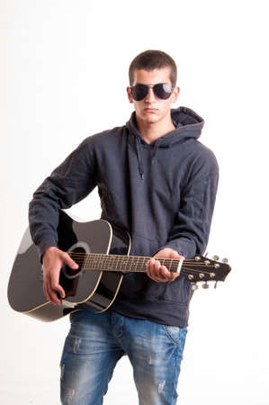 brunets: Image of teenager in black clothes, hoodie and sunglasses who is playing at guitar