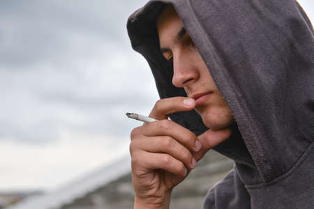 pensive and worried teenage boy with black hoodie is smoking cigarette outdoor. Harmful smoking concept