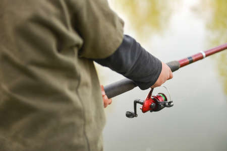 fishing reel: Closeup of fisherman`s hand holding rod with spinning. Fishing reel visible. Selective focus