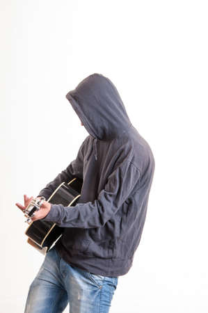 Sad teenager in hoodie playing acoustic guitar