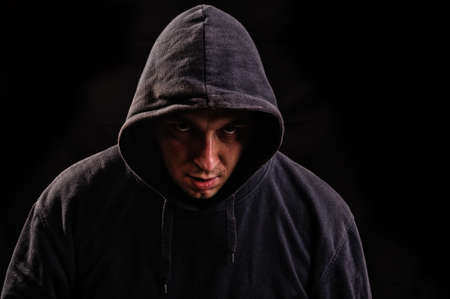 Silhouette of man in the hood or hooligan over dark background