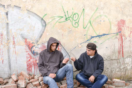 two street hooligans or rappers standing against a graffiti painted wall and sharing a cigarette