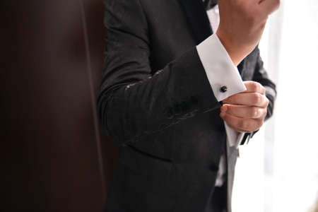 close up of a man who wears suit and white shirt and cufflink
