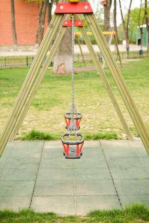children play area: Close up of empty swing in a children play area at park Stock Photo