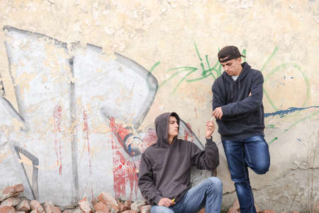 raperos: two street hooligans or rappers standing against a graffiti painted wall and sharing a cigarette