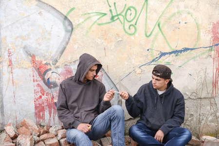 raperos: dos gamberros callejeros o los raperos de pie contra una pared de graffiti pintado y compartir un cigarrillo