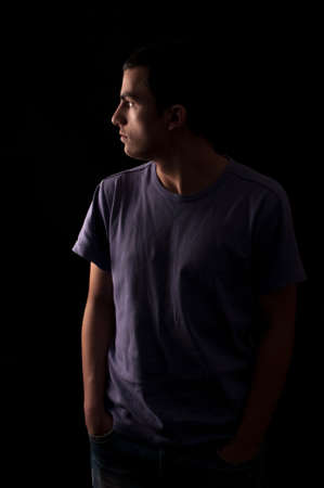 Portrait of young man wearing t-shirt standing with hands in pockets and looking on one side isolated on black background
