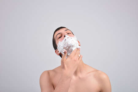 cheek: Closeup of a young man preparing to shave, he puts foam on his cheek Stock Photo