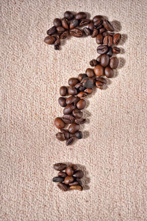 Question-mark symbol made from coffee crops on beige background