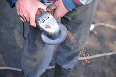 sharpen: Close up of a man sharpen an ax using electric grinder. Sparks while grinding iron. Selective focus