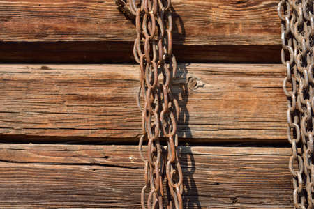rusty chain: Rusty chain hanging on old wooden wall