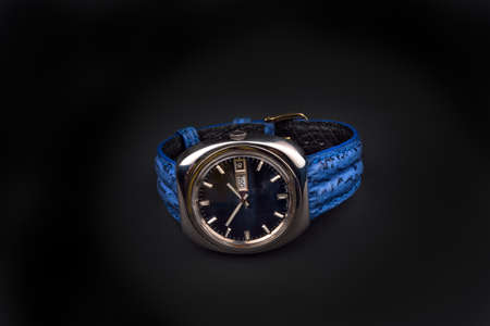 strap on: Old mens classic watch with blue strap on black background