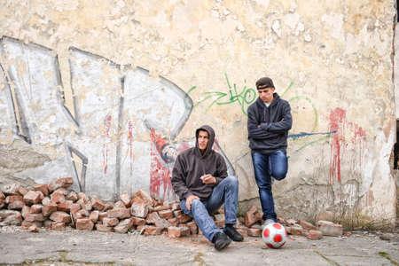 raperos: dos gamberros callejeros o los raperos de pie contra una pared de graffiti pintado se est�n preparando para fumar un cigarrillo