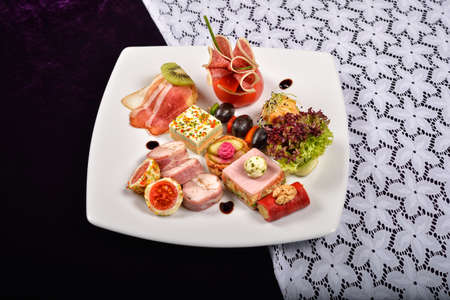 carnes y verduras: Antipasto and catering platter with different appetizers(fruits, vegetables, meats, cheeses)on white and purple background