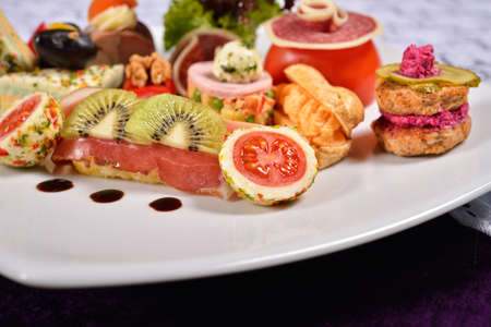 carnes y verduras: Close up of atipasto and catering platter with different appetizers (fruits, vegetables, meats, cheeses), restaurant menu Foto de archivo